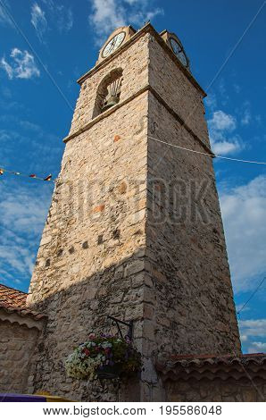 Close-up of church steeple on stone bricks at sunset, with clock and flags, in the lovely village of Gréoux-les-Bains. In Alpes-de-Haute-Provence department, Provence region, southeastern France