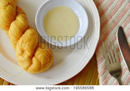 twist bread dipping with sweetened condensed milk on plate