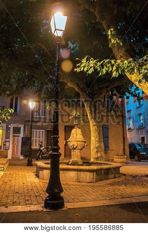 Rians, France - July 08, 2016. View of square with fountain in the early evening with lamp lit, at the lovely village of Rians. Located in Var department, Provence region, in southeastern France.