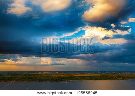 Evening landscape with a beautiful stormy sky and a river