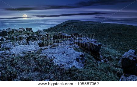huge boulders on the edge of hillside at midnight. fine weather in summer mountain landscape at night in full moon light