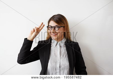 Indoor shot of successful and attractive young businesswoman wearing eyeglasses and formal jacket smiling broadly showing victory sign at camera posing against white studio wall background