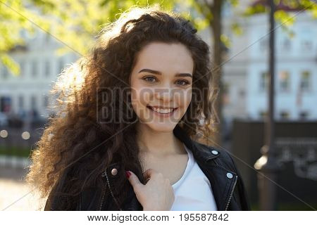 Trendy-looking gorgeous hipster girl wearing her long curly hair loose having walk on city streets enjoying first sunny days after heavy rains. People leisure and modern urban lifestyle concept