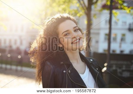 Street style and fashion concept. Headshot of attractive cheerful young female model dressed in black leather jacket posing outdoors in urban surroundings looking and smiling broadly at camera