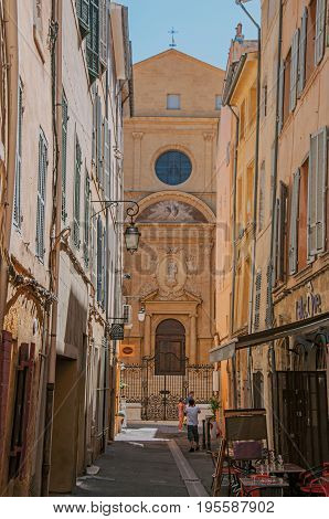 Aix-en-Provence, France - July 09, 2016. Alley with church in the background in Aix-en-Provence, a lively town in the countryside. In Bouches-du-Rhone department, Provence region, southeastern France
