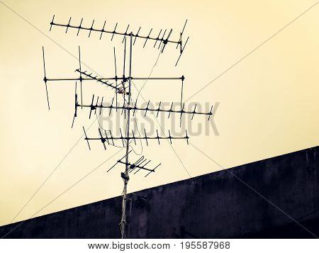 Vintage look filter, Old antenna with sky background. Silhouetted image