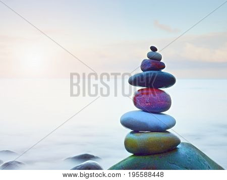 Balanced Stone Pyramide On Shore Of Blue Water Of Ocean. Blue Sky In Water Level Mirror