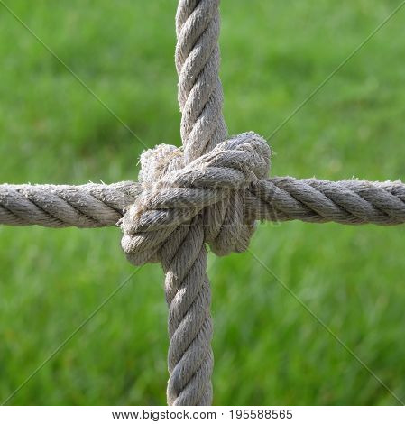 Rope knot with green garden background,as a symbol for trust teamwork harmony or collaboration.