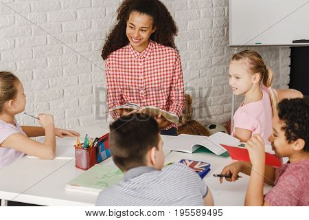 Young teacher reading book to her young students
