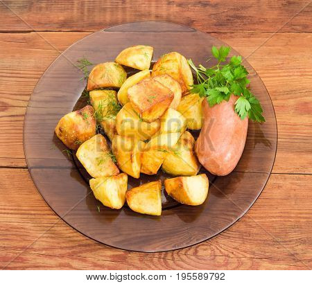 Top view of the dark glass dish with fried potatoes sprinkled by chopped dill fried wieners and twig of parsley closeup on a surface of old wooden planks