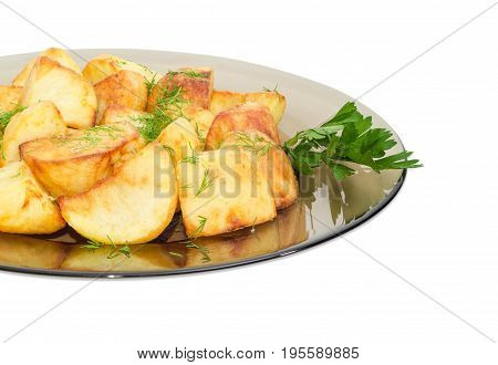 Fragment of the dark glass dish with fried potatoes sprinkled by chopped dill and twig of parsley on a light background