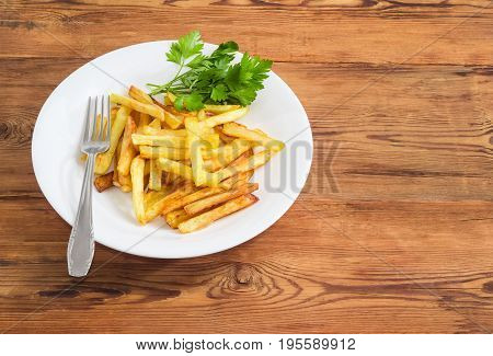 French fries with several twigs of parsley on the white dish and fork of stainless steel on a surface of old wooden planks