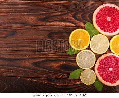 A view from above on various citruses on a dark wooden background. Red grapefruits with a juicy texture. Sour yellow lemons and sweet oranges laying on a table. Tropical summer fruits.