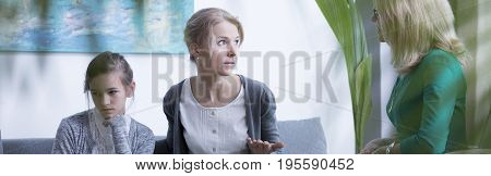 Middle-aged mother and teenage daughter talking during psychotherapy in office