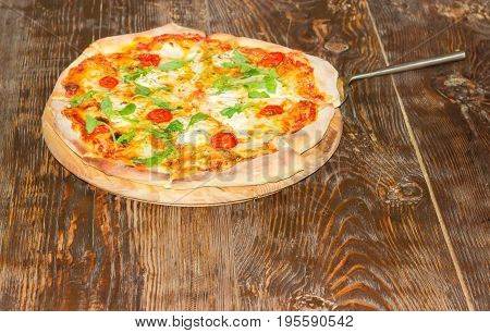 Cooked round pizza with tomatoes cheese and arugula and pizza spatula on the old wooden table