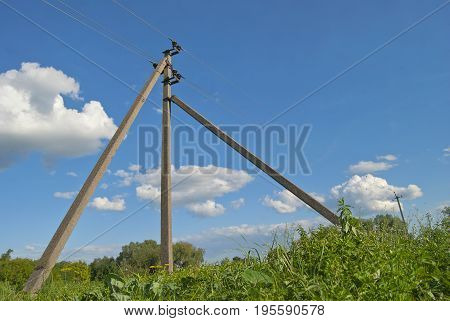 Concrete pillar of power line with open wires against the blue sky.