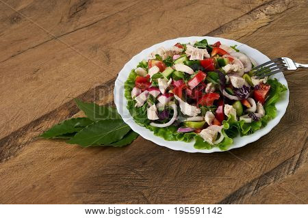 Summer fresh salad made of tomato ruccola chicken breast arugula crackers and spices and other different vegetables on wooden background