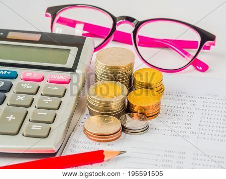 abstract money saving. financial statement with stack of coins calculator glasses and red pencil on white background.