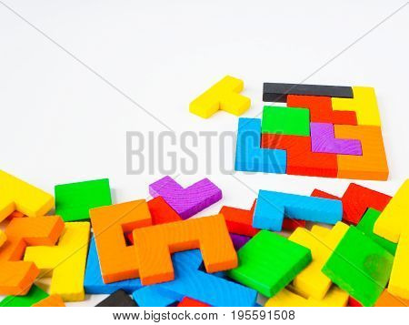 Education concept- The last piece to complete a square tangram puzzle colorful wooden puzzle for kid on white background