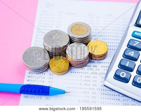 abstract money saving. financial statement with stack of coins calculator and blue pen on pink background.