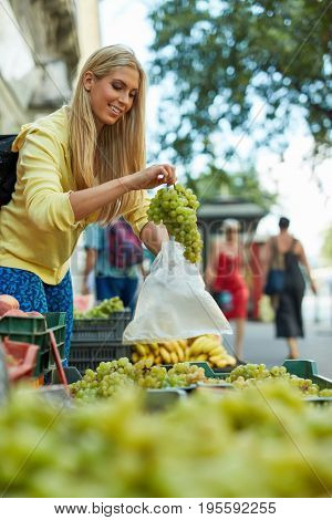 Young blonde woman buying grapes at fruit market.