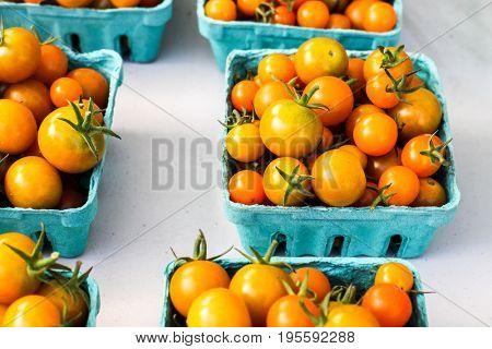 Yellow tomatoes from farms market in paper container