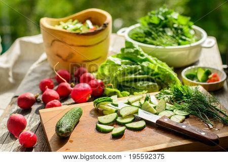 cooking fresh vegetables salad on a wooden table in the countryside