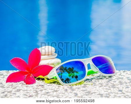 Sunglasses with red frangipani (plumeria) flowers and stack of stone at the side of swimming pool. Vacation beach summer travel concept