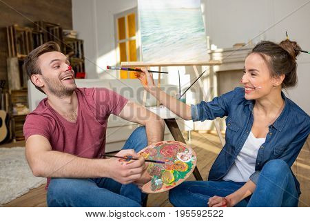 Happy Young Couple With Paintbrushes And Palette Having Fun While Sitting On Floor