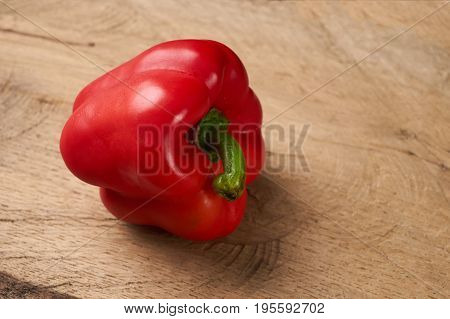 Sweet bulgarian red bell pepper on wooden background
