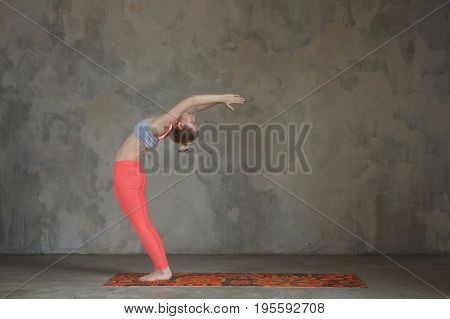 Young Woman Practicing Hasta Uttanasana, Raised Arms Yoga Pose Against Texturized Wall / Urban Backg