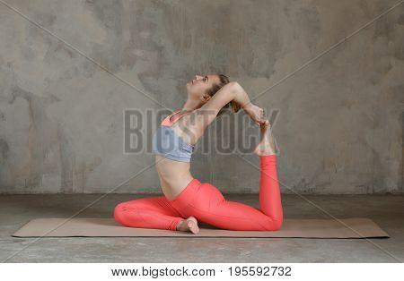 Young Woman Practicing Yoga One-legged King Pigeon Pose /.eka Pada Rajakapotasana Against Texturized
