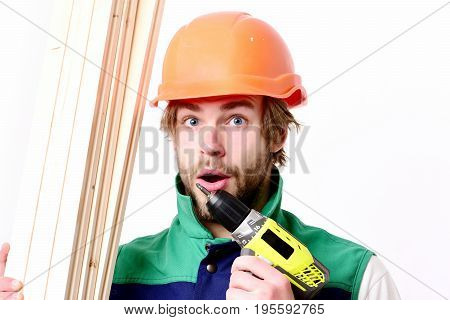 Man with surprised face expression. Builder in orange helmet and uniform isolated on white background. Construction worker holds wooden boards and yellow drill. Finished work and building concept