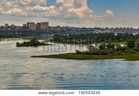 Cityscape of Irkutsk with blue sky and clouds and river with waves and green island