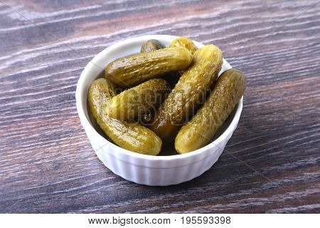 Pickles. Bowl with pickled gherkins, cucumbers on wooden background close up.