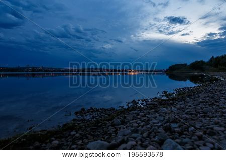 Sky after sunset at the bank of river Angara in Irkutsk with reflecton of clouds in water