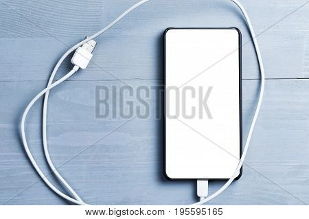 Bezel less smart phone with blank screen and power cable on a wooden background.