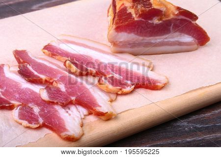 Fresh homemade smoked bacon with leaves lettuce on a wooden cutting board. Selective focus