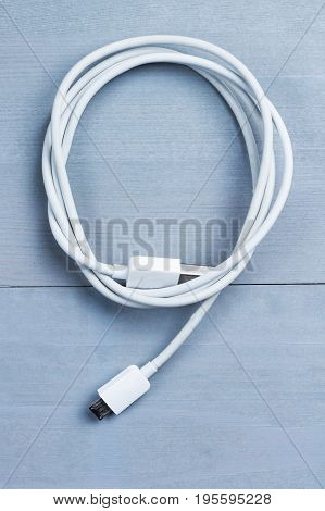 Flatlay of micro usb smart phone power cable on a wooden background. Idea concept.