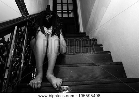 Girl Sitting On Ladder In House With Arm Around Knee And Lower Head, Child Abuse
