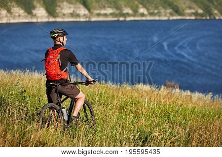 Active bicyclist at the riverside. Moutnain bike cyclist has adventure at summer day