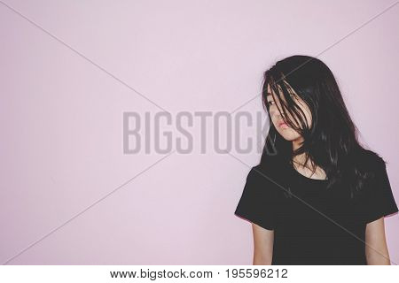 depress and hopeless girl with absent minded looking down stand on pink background in whit e tone