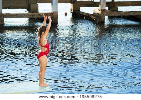 Little caucasian 6 years old girl preparing for jump into the sea from springboard. Summer sport camp on the beach.