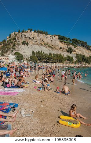 Cassis, France - July 09, 2016. Bathers on the pebble beach with castle in the background in Cassis, a beautiful and sunny seaside town with harbor. Provence region, southeastern France