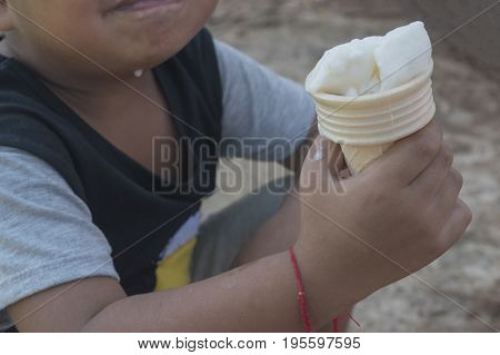 Little kid eating ice cream with selective and soft focus.