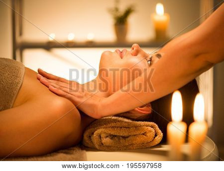 Spa woman Massage. Face Massage in beauty spa salon. Female enjoying relaxing body  massage in spa center. Body care, skin care, wellness, beauty treatment