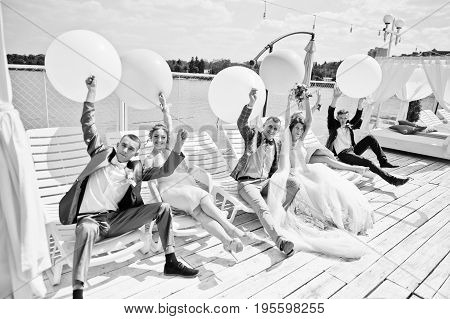 Wedding Couple, Groomsmen And Bridesmaids Having Fun With Balloons On Wharf. Black And White Photo.