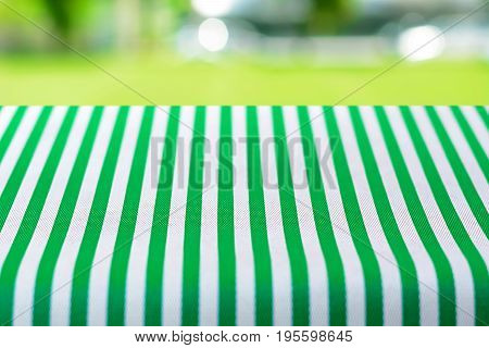 Table top covered with striped tablecloth on blurred green yard background - can be used for montage or display your products