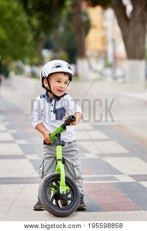 Little boy kid in helmet ride a bike in city park. Cheerful child outdoor. Happy childhood concept
