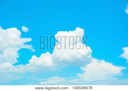 White puffy clouds on bright summer blue sky background